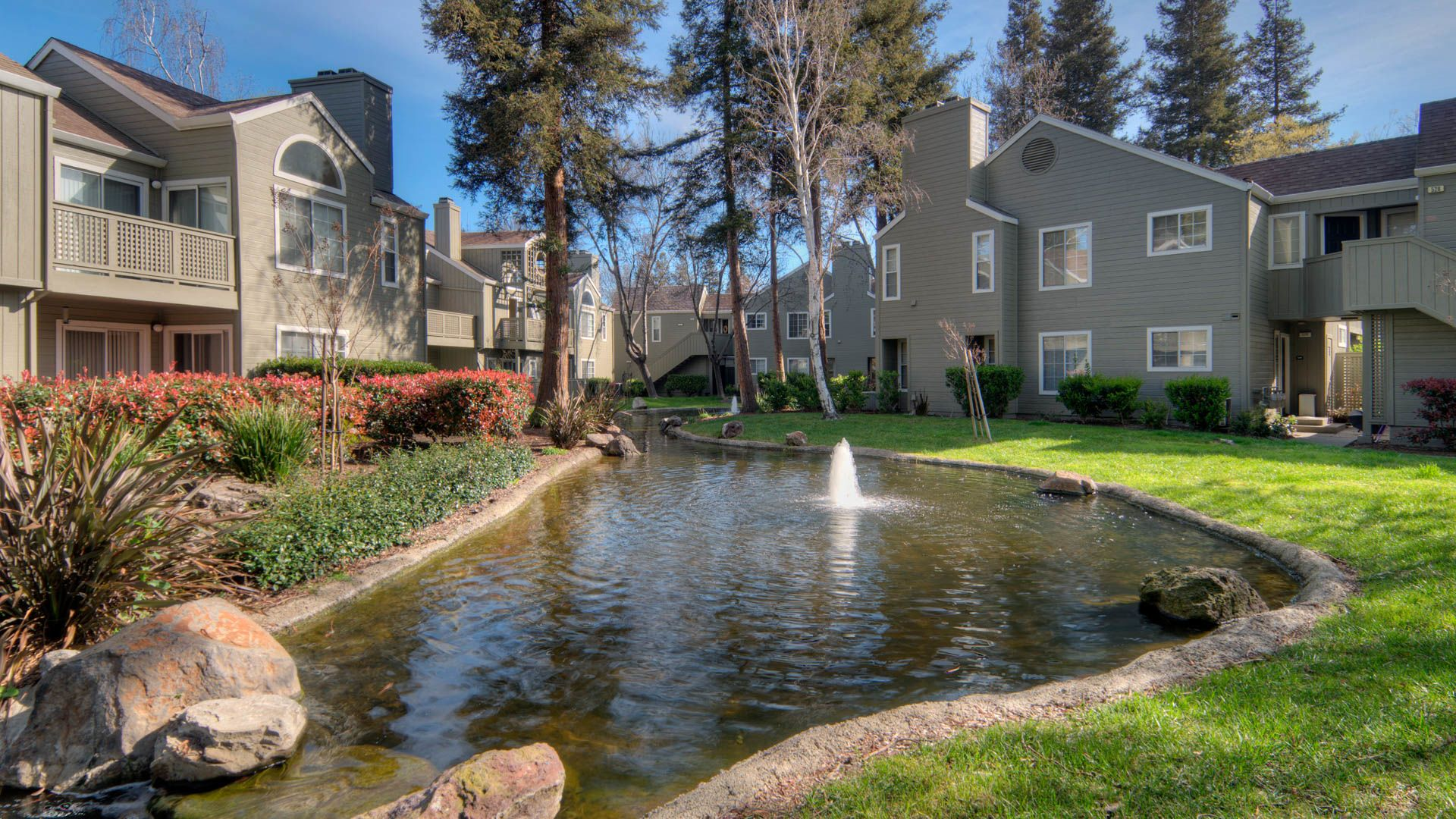 Wood Creek Apartments - Building Exterior with Pond