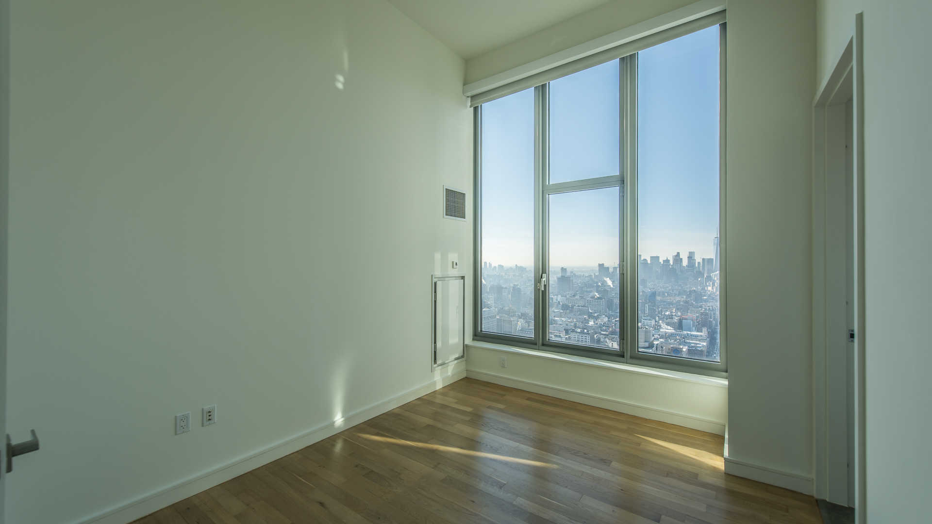 Bedroom with Oversized Windows and Hardwood Flooring